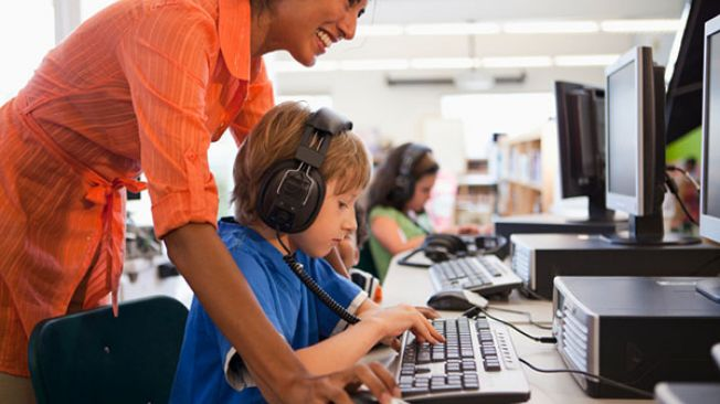 Young boy with headphones at computer, teacher looking over his shoulder at the screen