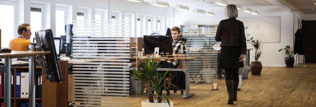 Open plan office with people at desks and woman walking away