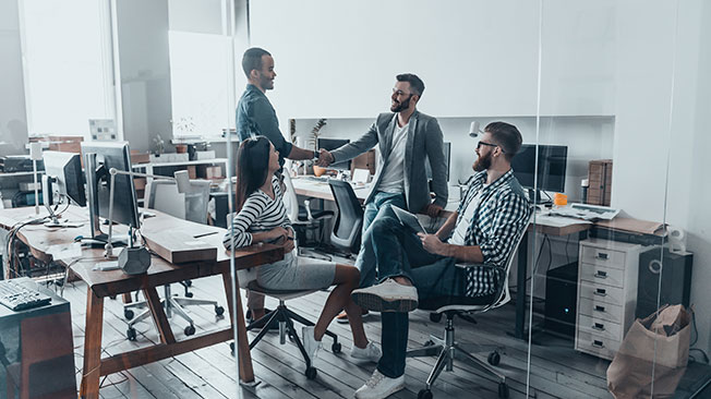 Relaxed business meeting with four people in an office, two of them shaking hands