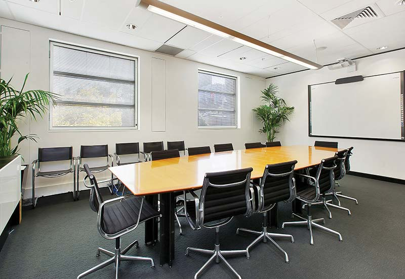 Boardroom at Screenrights office - large table with 12 chairs around it, 5 extra chairs along wall, whiteboard and plants