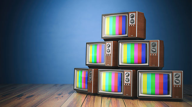 Stack of vintage televisions with colour bars on screen